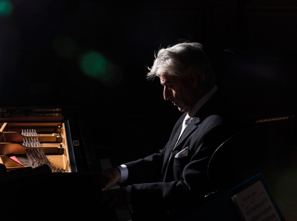 Photo of Marios Papadopoulos playing piano under a spotlight