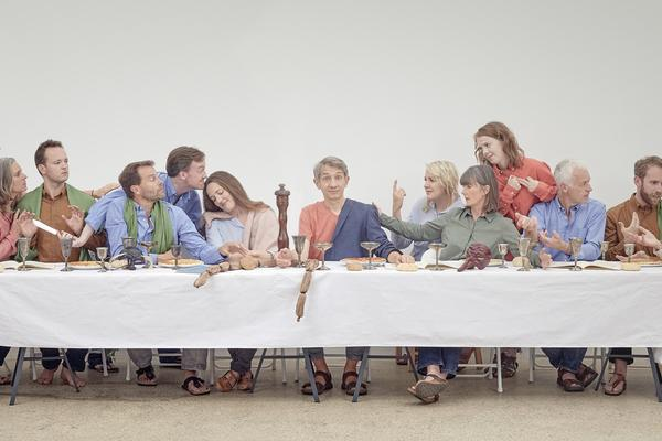 Image of people sitting on a long table, engaging in conversation