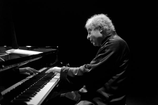 Black and white photo of Sir Andras Schiff playing piano