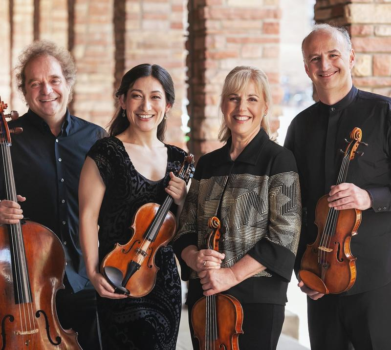 Photo of a string quartet holding their instruments (two violins, a viola and a cello)