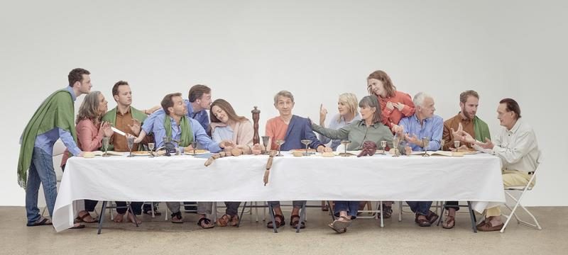Photo of people sitting on a long table engaging in conversation, replicating Leonardo Da Vinci's 'The Last Supper' paining