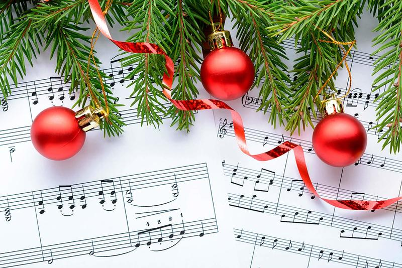 Image of sheet music with red baubles and ribbons