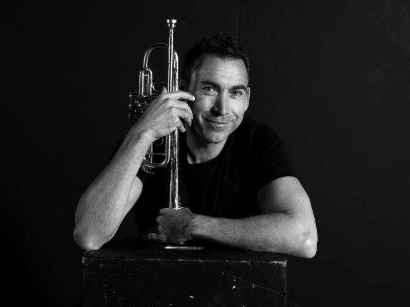 Photo of Paul Merkelo holding a trumpet against a black background